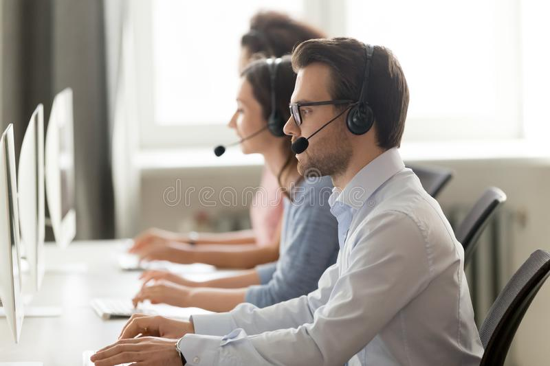 Male call center agent in wireless headset consulting online client stock photos