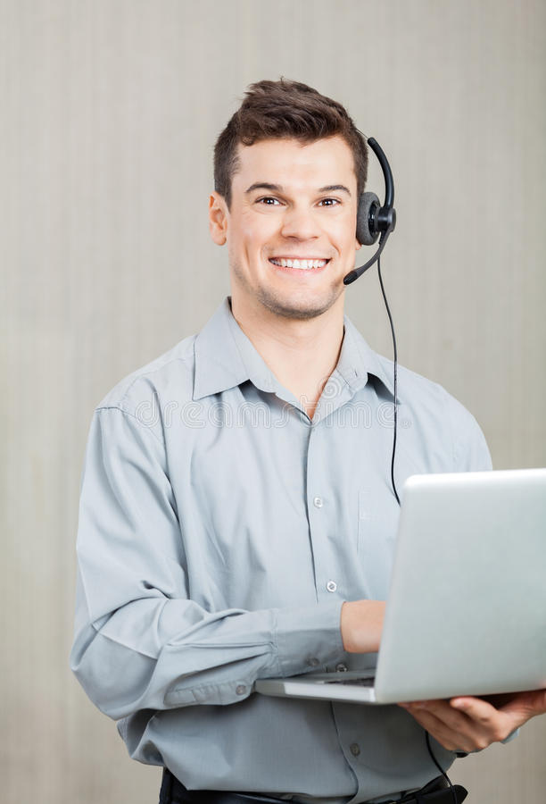 Male Call Center Employee With Laptop. Portrait of happy male call center employee with laptop standing in office stock photo