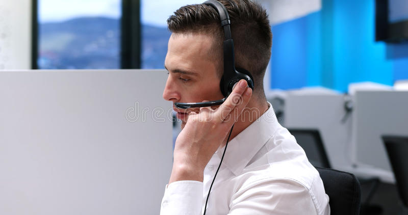 Male call centre operator doing his job. Young smiling male call centre operator doing his job with a headset royalty free stock images