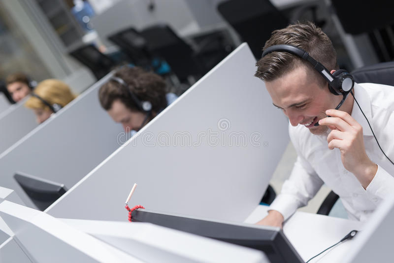 Male call centre operator doing his job. Young smiling male call centre operator doing his job with a headset royalty free stock photo