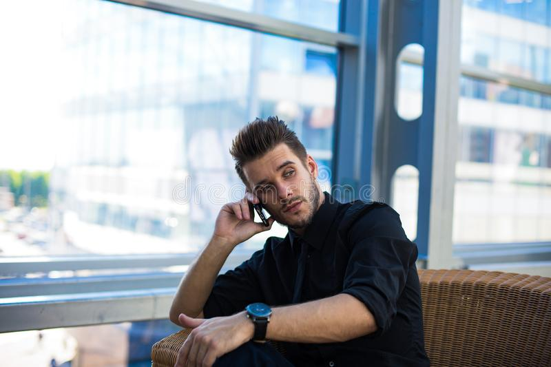 Male calling via cellphone while waiting meeting with client royalty free stock image