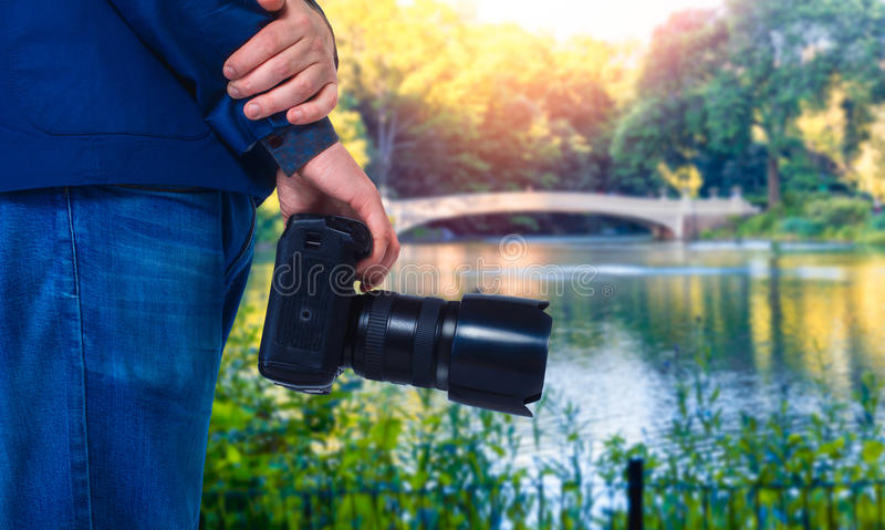 Male cameraman hands with digital camera. Closeup, green nature and lake on background stock images