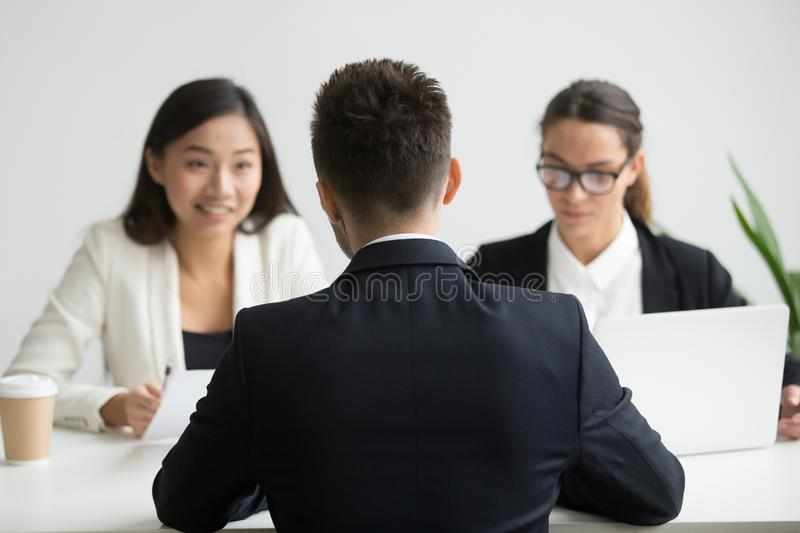 Male candidate interviewed by diverse HR team royalty free stock image