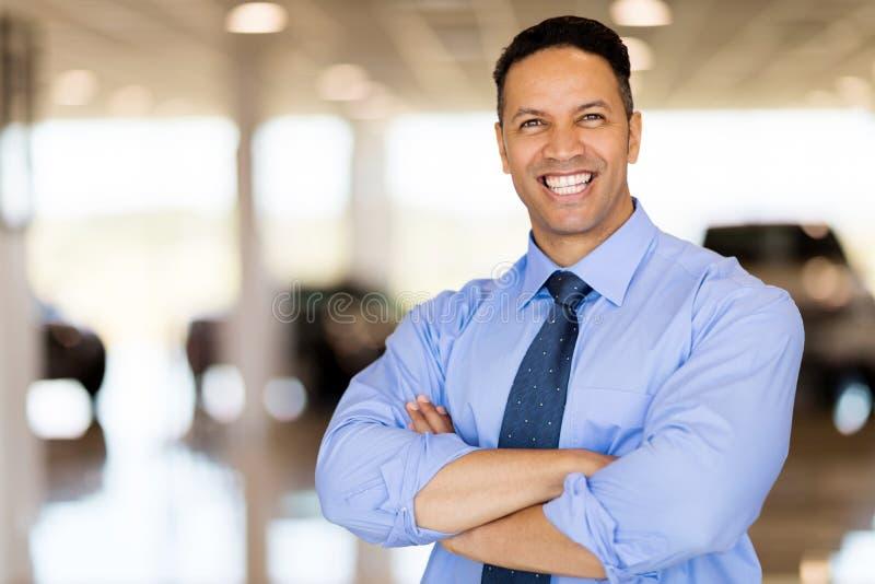 Male car dealer principal. Good looking male car dealer principal inside showroom stock photo
