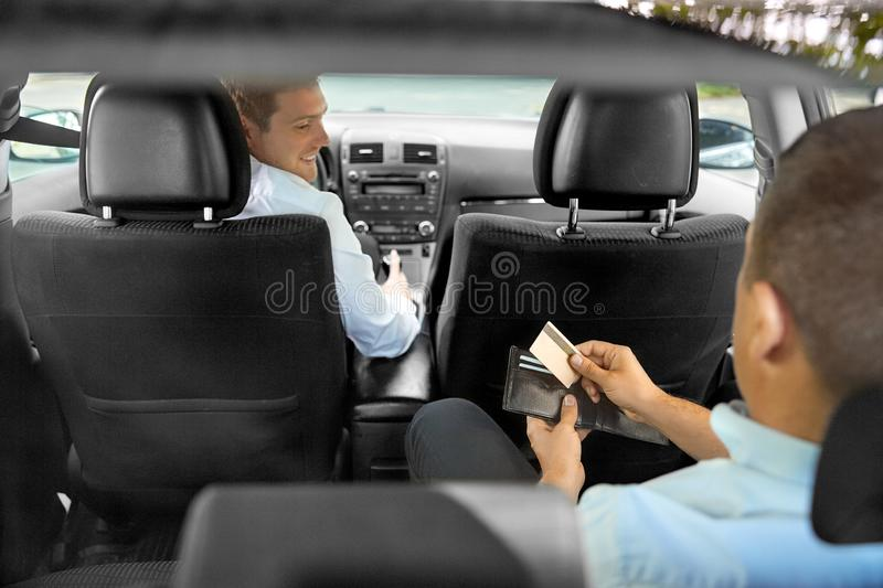 Male car driver looking at passenger with wallet. Transportation, taxi and payment concept - male car driver looking at passenger with credit card in wallet stock photography