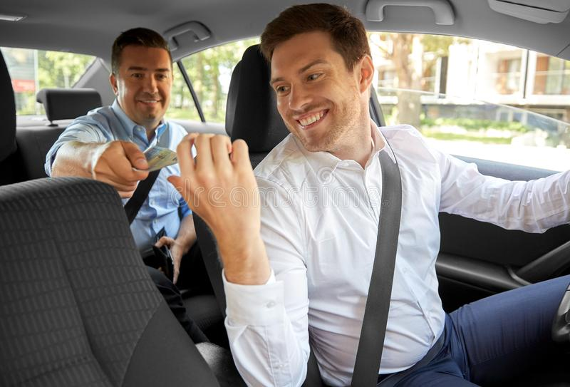 Male car driver taking money from passenger. Transportation, taxi and payment concept - male car driver taking money from passenger royalty free stock photo