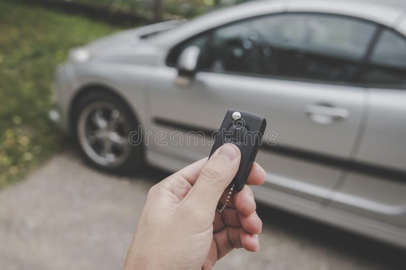 Male car owner switches off the alarm system and unlocks the doors of the car using remote control keys on a parking stock photography