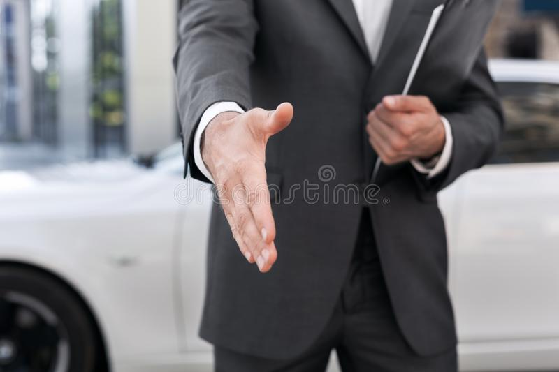 Male car salesman stretching hand for handshake stock photo