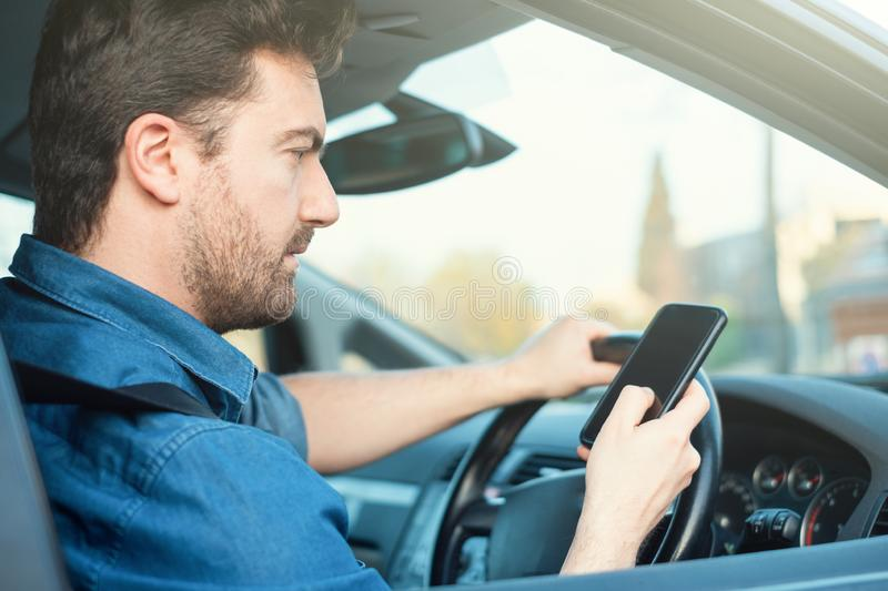Male in car using mobile phone at the wheel stock images
