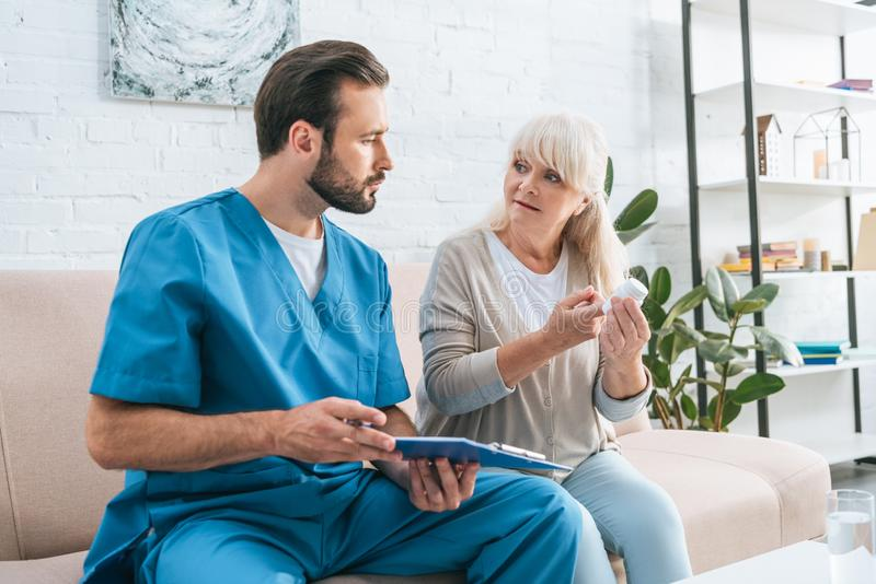Male caregiver with clipboard looking at senior woman. Holding pills stock photography