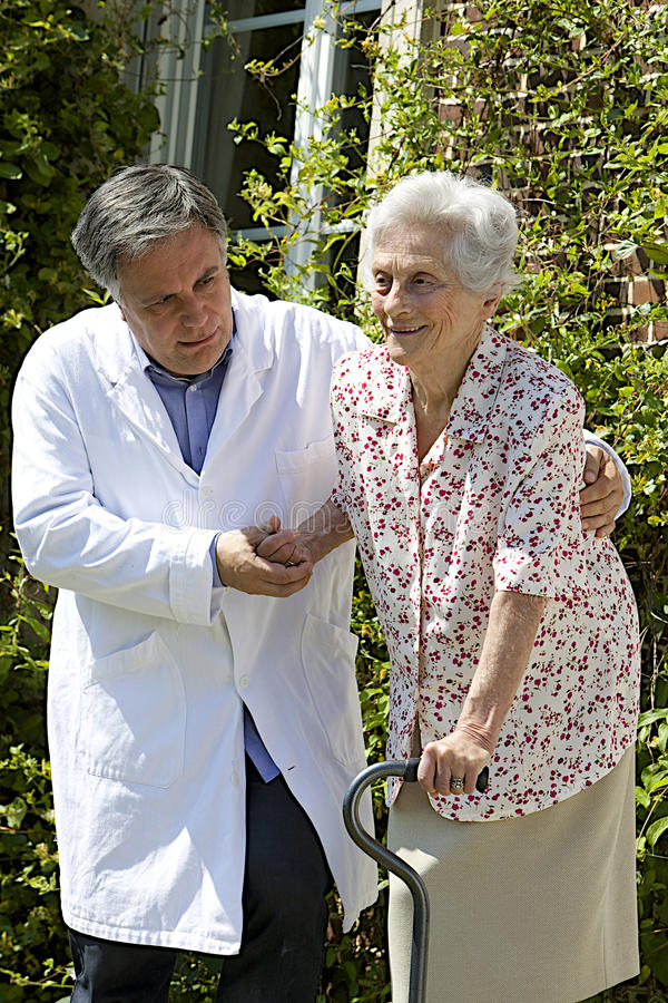 Male caregiver helping a senior patient with her walking stick. Male caregiver helping senior patient with walking stick on the stairs outdoors stock photos