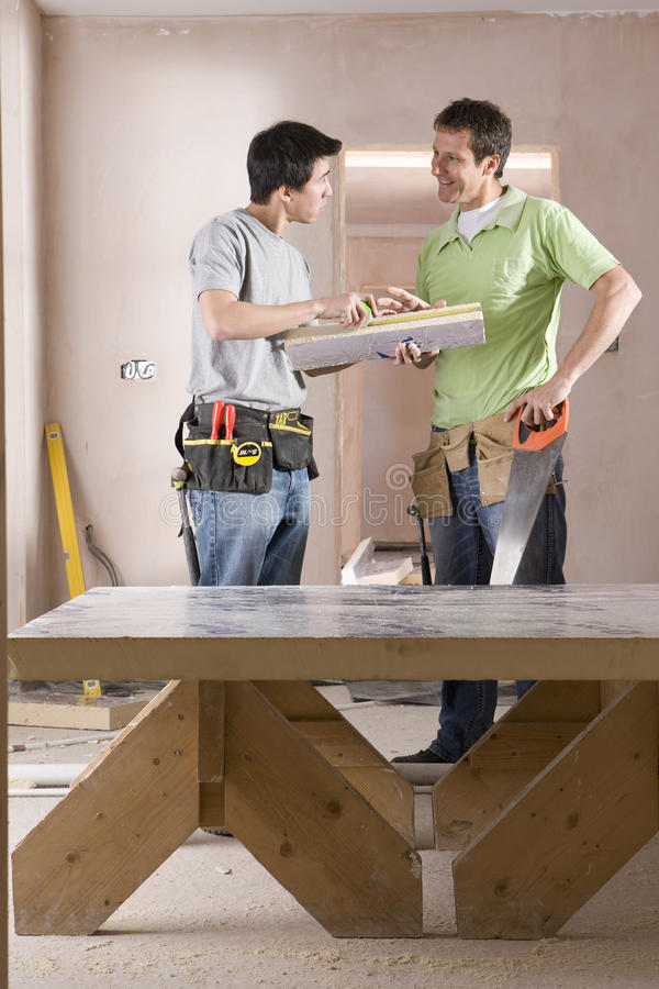 Male carpenter and apprentice with tools talking next to sawhorse stock images