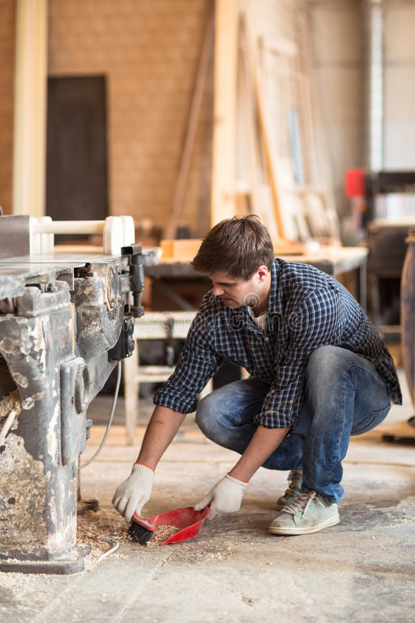 Male carpenter in the carpentry workshop is sweeping the sawdust royalty free stock image