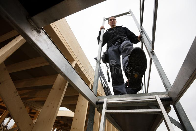 Male Carpenter Moving Down Ladder Of Incomplete Building. Low angle view of male carpenter moving down ladder of incomplete building stock photos
