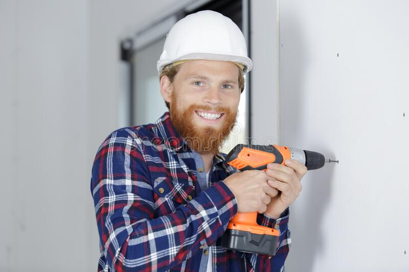 Male carpenter using drill on wall stock photography