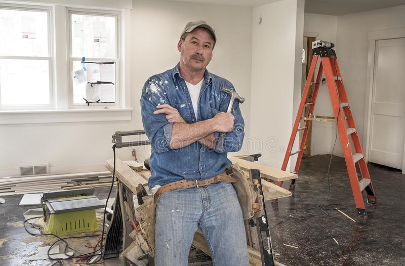 Male carpenter wearing leather tool belt and holding hammer lean royalty free stock photography