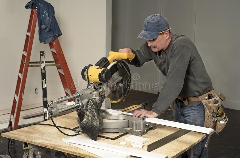 Male carpenter wearing tool belt and cutting wood board with professional chop saw on construction site home remodel royalty free stock photos