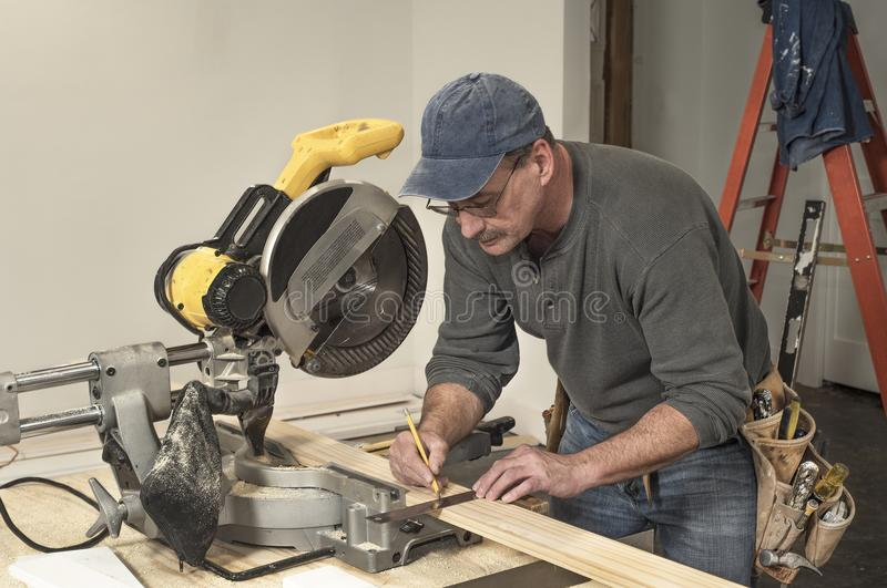 Male carpenter wearing tool belt and using square tool to mark wood board for cutting on professional chop saw stock images