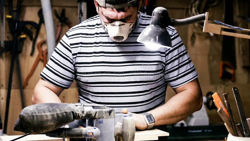 Craftsman working with grinding machine at wood workshop. stock photo