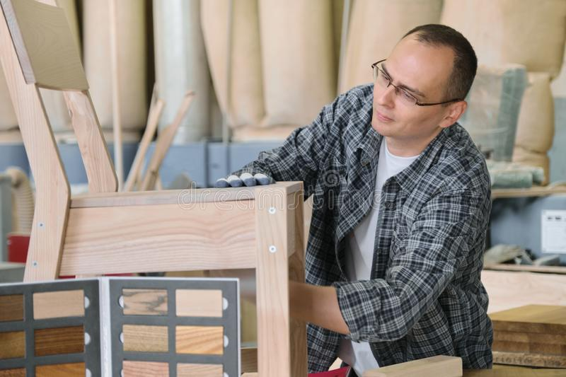 Male carpenter working in furniture joinery, master making wooden chair in wood workshop royalty free stock image