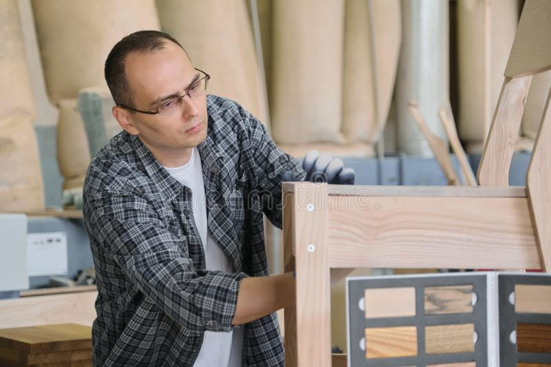Male carpenter working in furniture joinery, master making wooden chair in wood workshop.  stock photos