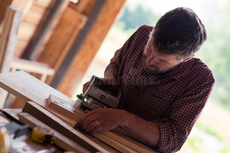 Male Carpenter working on planks stock photo