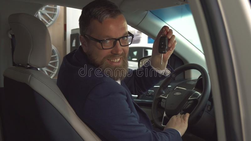 Male customer shows key inside the car stock photography