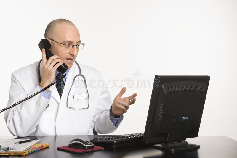 Male Caucasian doctor. Caucasian mid adult male physician sitting at desk with laptop computer talking on telephone royalty free stock photo