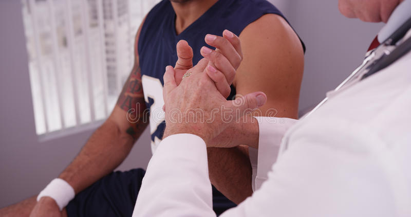 Male caucasian doctor checking wrist of male african sports athlete.  royalty free stock photography