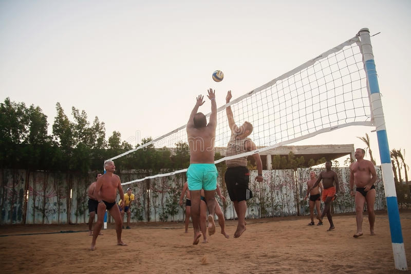 Male Caucasians, Arabs, Africans playing volleyball on the beach at sunset. Egypt. Hurghada. Golden 5 October 7, 2016. Male Caucasians, Arabs, Africans and stock photography