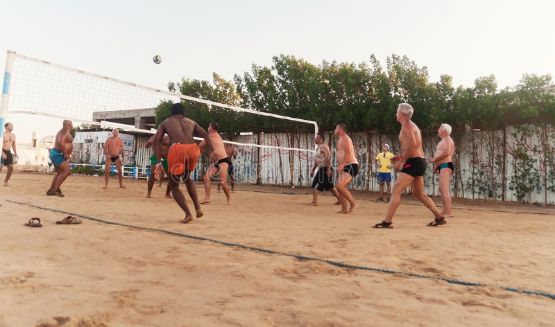 Male Caucasians, Arabs, Africans playing volleyball on the beach at sunset. Egypt. Hurghada. Golden 5 October 7, 2016. Male Caucasians, Arabs, Africans and royalty free stock photography
