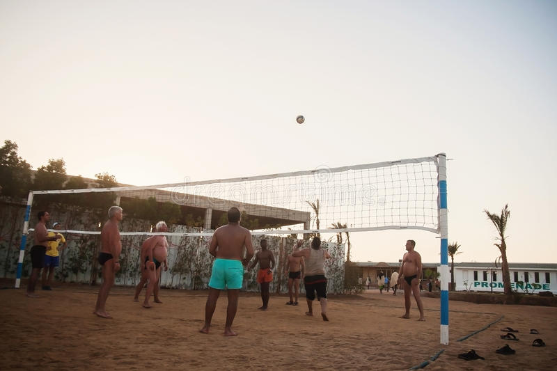 Male Caucasians, Arabs, Africans playing volleyball on the beach. Male Caucasians, Arabs, Africans and playing volleyball on the beach at sunset. Egypt. Hurghada stock photo