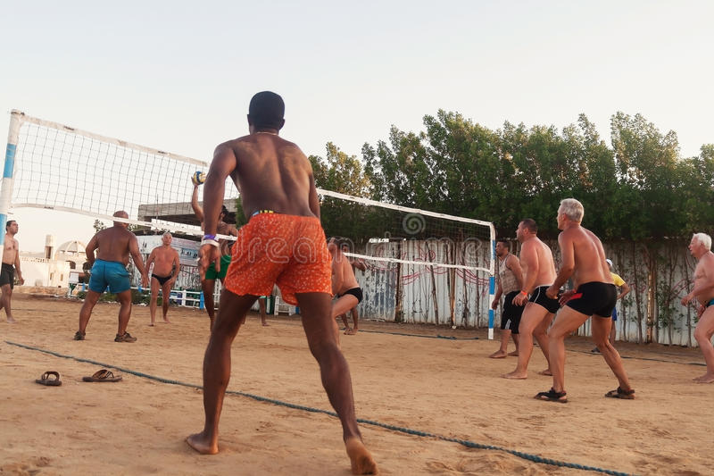 Male Caucasians, Arabs, Africans playing volleyball on the beach. Male Caucasians, Arabs, Africans and playing volleyball on the beach at sunset. Egypt. Hurghada stock images