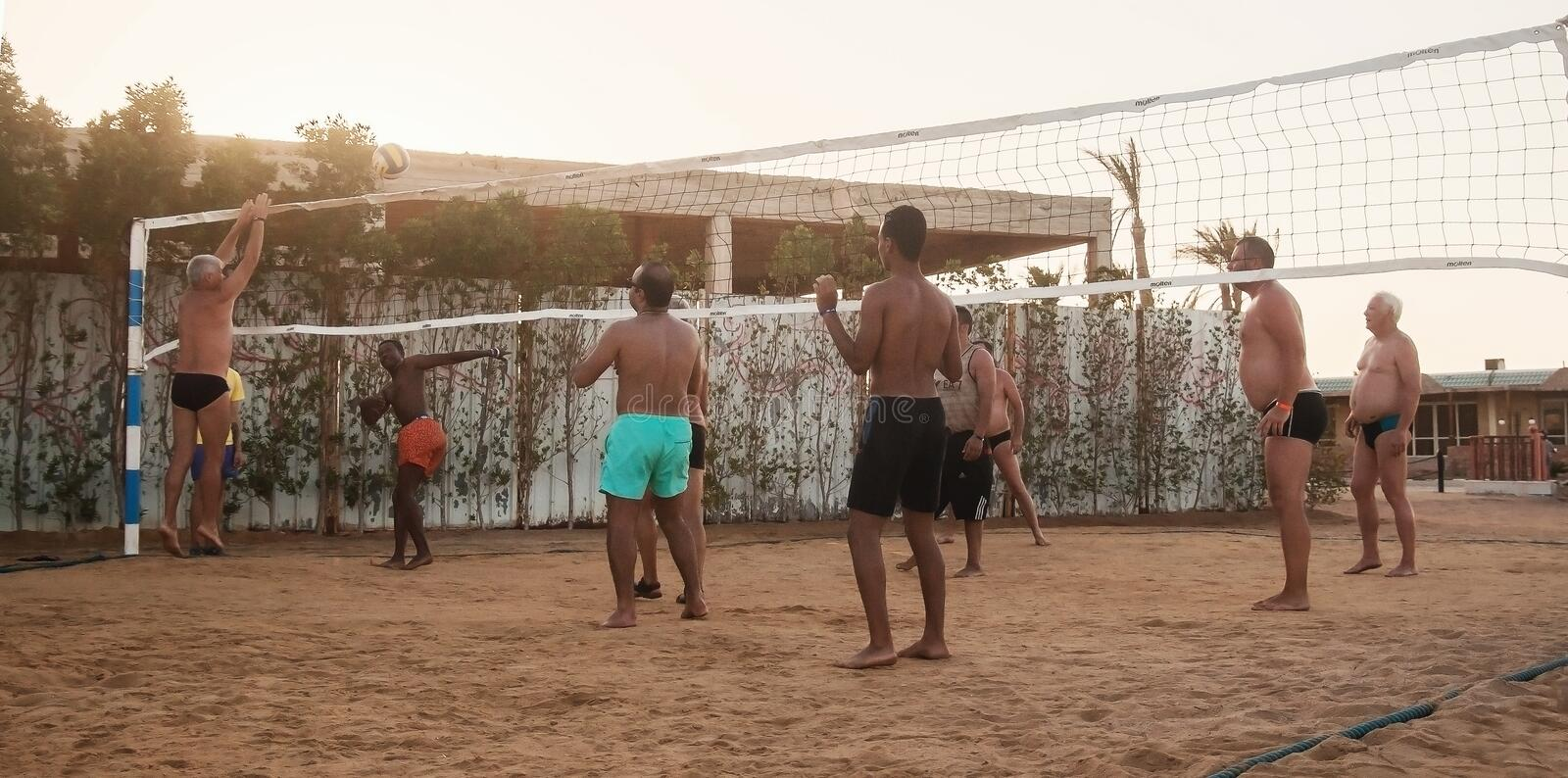 Male Caucasians, Arabs, Africans playing volleyball on the beach. Male Caucasians, Arabs, Africans and playing volleyball on the beach at sunset. Egypt. Hurghada royalty free stock photo