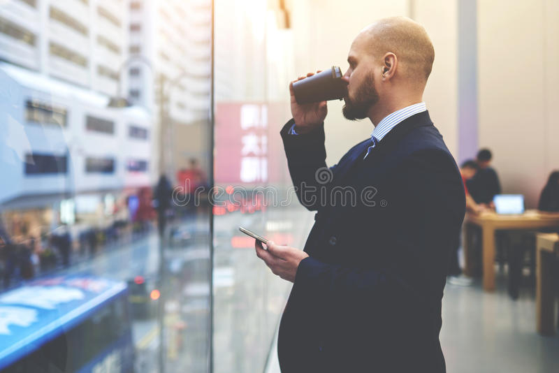 Male CEO with cell telephone in hand is thinking about job plan. Man owner of successful enterprise is waiting for a all on mobile phone, while is watching on royalty free stock photos