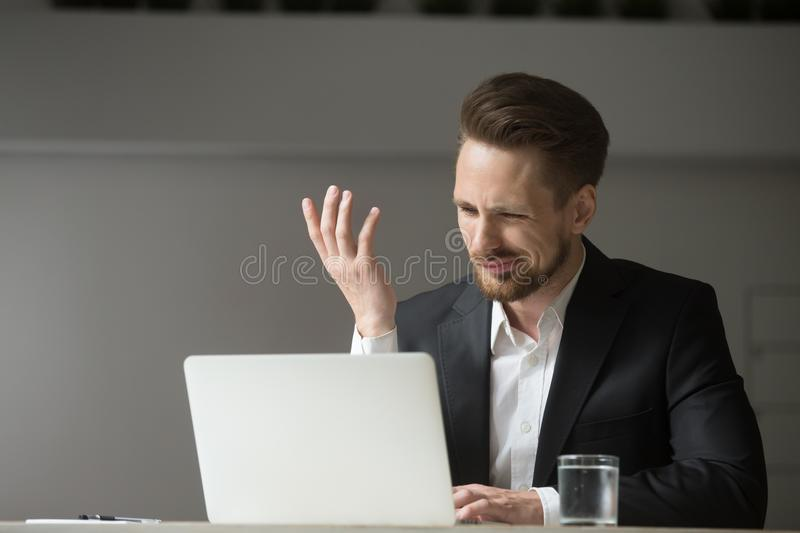 Male CEO confused about his business crisis. Angry client or confused male CEO showing misunderstanding and annoyance reading financial failing reports on laptop royalty free stock photo