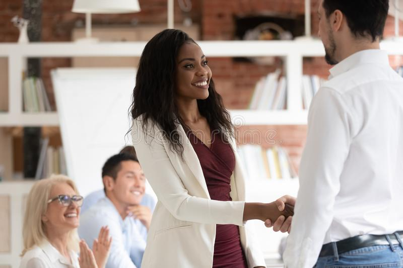 Male ceo handshake black female employee greeting at meeting. Male company ceo or boss shake hand of excited african American female employee congratulating with stock photo
