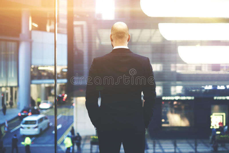 Male CEO is looking at active life of the main street Hong Kong outside the window royalty free stock photos