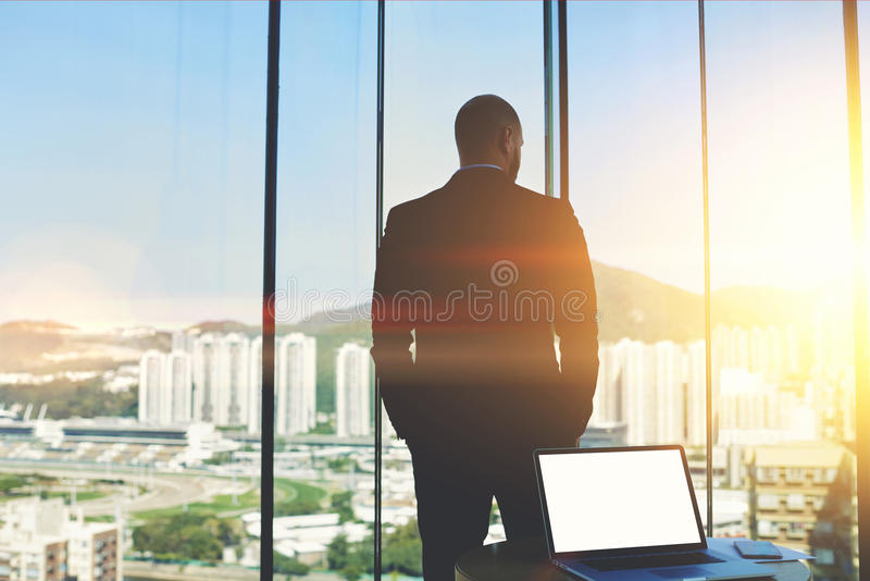 Male CEO is resting after conference with staff. Back view of a man is thinking about the future importance of signing a contract with international partners royalty free stock image