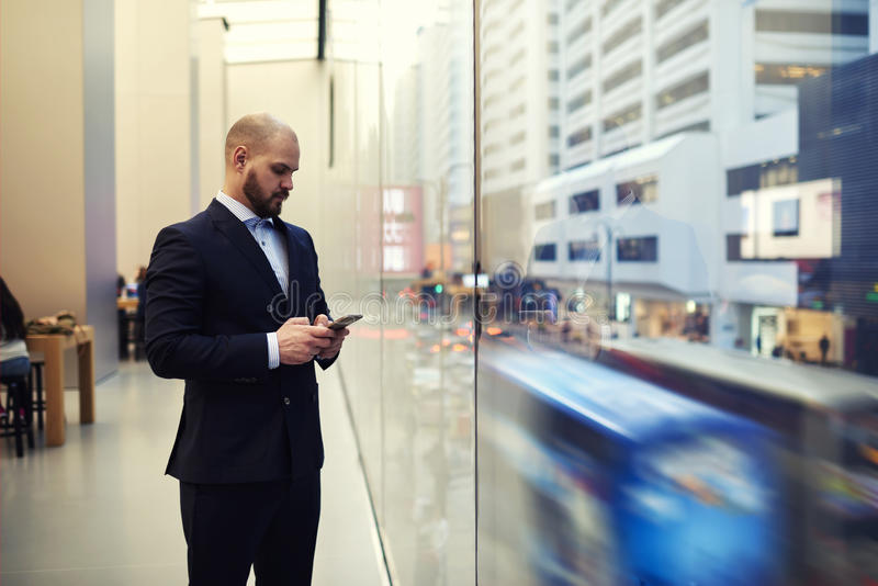 Male CEO is standing near window with view of a big metropolitan city in action. Young man owner of successful enterprise is typing on mobile phone text message stock photography