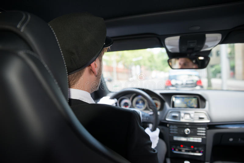Male Chauffeur In Car. Rear View Of A Male Chauffeur Driving A Car royalty free stock image