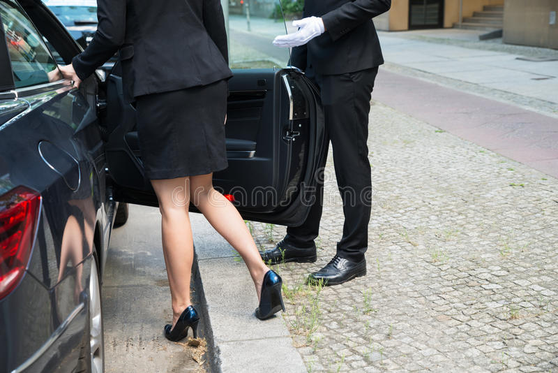 Male Chauffeur Opening The Car Door. For The Businesswoman On Street stock photos