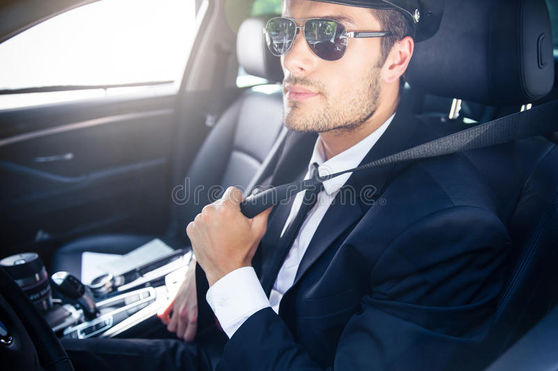 Male chauffeur sitting in a car. Portrait of a handsome male chauffeur in sunglasses sitting in a car stock photography