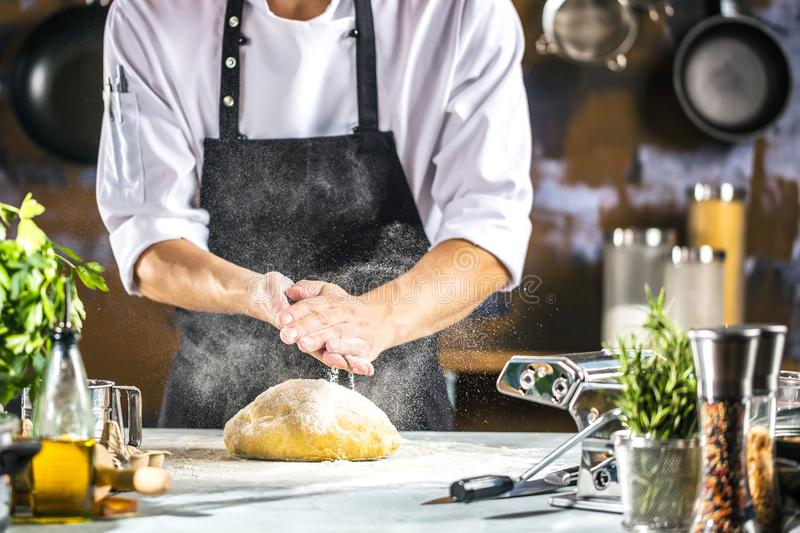 Chef preparing dough for pizza or pasta in the restaurant kitchen royalty free stock images