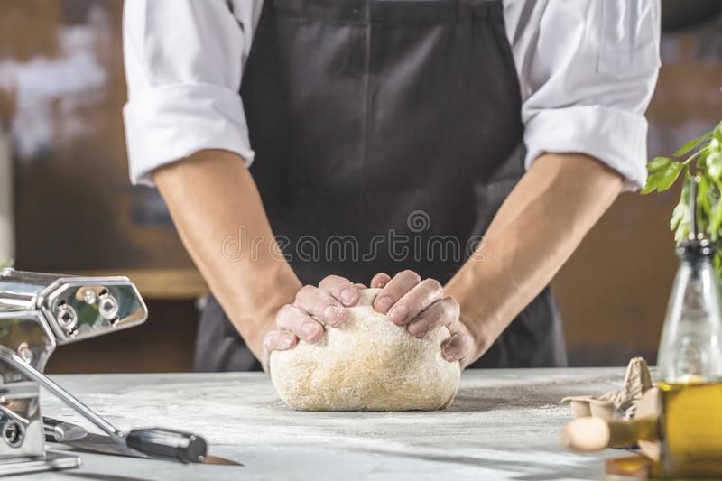 Chef preparing dough for pizza or pasta in the restaurant kitchen royalty free stock image
