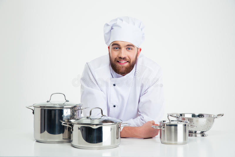 Male chef cook sitting at the table with dishes stock images