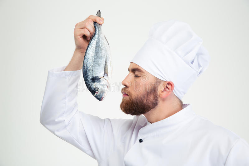 Male chef cook smelling fresh fish royalty free stock photo