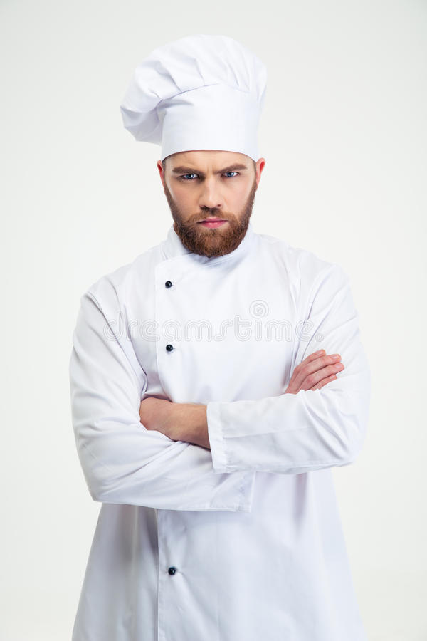 Male chef cook standing with arms folded. Portrait of angry male chef cook standing with arms folded isolated on a white background stock images