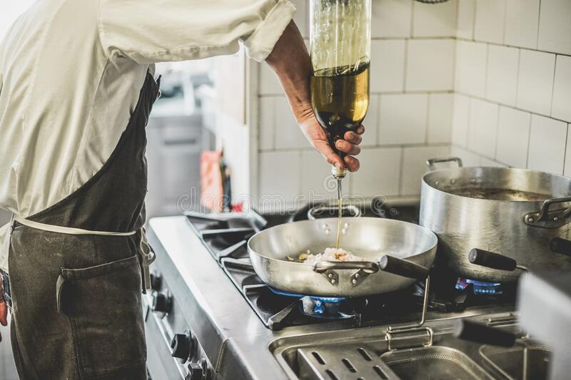 Male chef cooking fresh fish sauce in restaurant kitchen - Cook at work during dinner service - Italian style cuisine, lifestyle. And healthy food concept royalty free stock photography