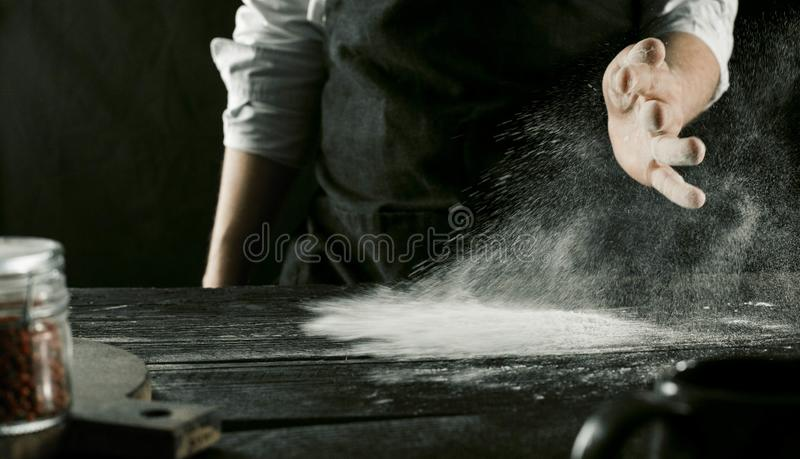 Male chef hands pouring flour on kitchen table. Side view stock photo